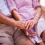 Cropped shot of a senior couple sitting close together and holding hands lovingly